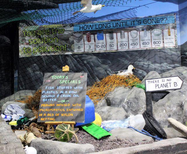 """Hinweisschild """". """"You are the solution to pollution"""",. Darunter Hinweise zu den Jahren, die Plastik im Meer zur Zersetzung braucht. Darunter einige einzelne Objekte aus Plastik und Metall."""