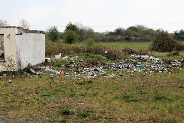 Links im Bild die helle Wand einer Hazsruine, daneben auf dem Gras Müll aller Art.