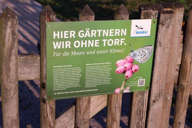 Grünes Hinweisschild an einem Gartentor aus Holz: 'Hier gärtnern wir ohne Torf'.
