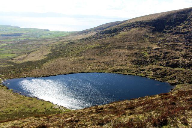 Kleiner See, der blau schimmert, iumgeben von grünen Abhängen inr den Bergen.