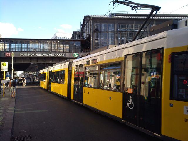 Gelb-weiße Straßenbahn in Berlin vor dem Bahnhof Friedrichstraße.