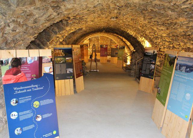 Informationstafeln mit Texten und Fotos in einem Gewölbekeller aus Steinquadern.