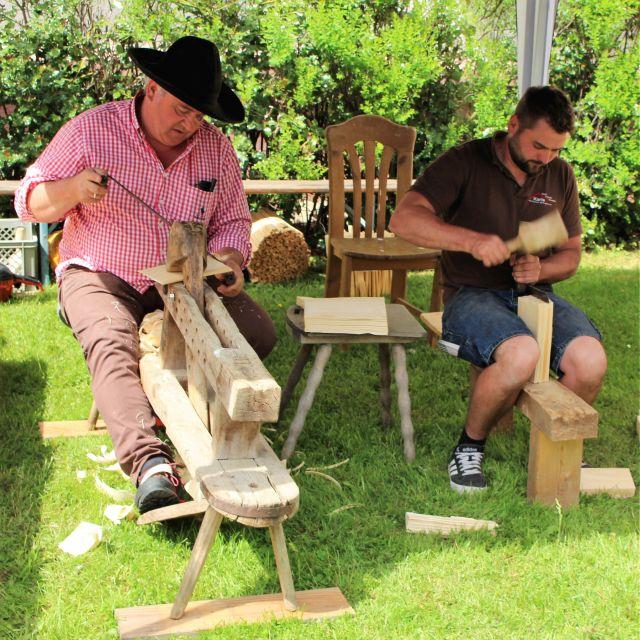 Ein Mann mit Hut und einem rot-weißen Hemd stellt Schindeln her. Neben ihm ein jüngerer Mann mit dunklerem Hemd, der die Vorarbeiten erledigt: er spaltet den Holzblock in dünne 'Platten'.