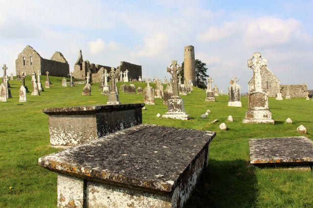 Im Vordergrund steinerne Gräber - einem Sarkophag ähnlich - auf einer grünen Wiese. Dahinter Rundturm, Ruinen der Kirchen und Kapellen sowie weitere Gräber zum Teil mit hochstehenden Kreuzen.