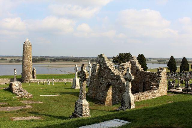 Im Hintergrund der Shannon und ein gemauerter Rundturm. Im Mittelpunkt die Ruine einer Kapelle. Daneben irische Hochkreuze.