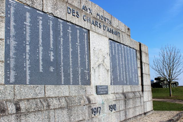 An einer Steinmauer ist eine große dunkle Tafel mit den Namen gefallener Soldaten angebracht. Im Hintergrund ein Panzer.