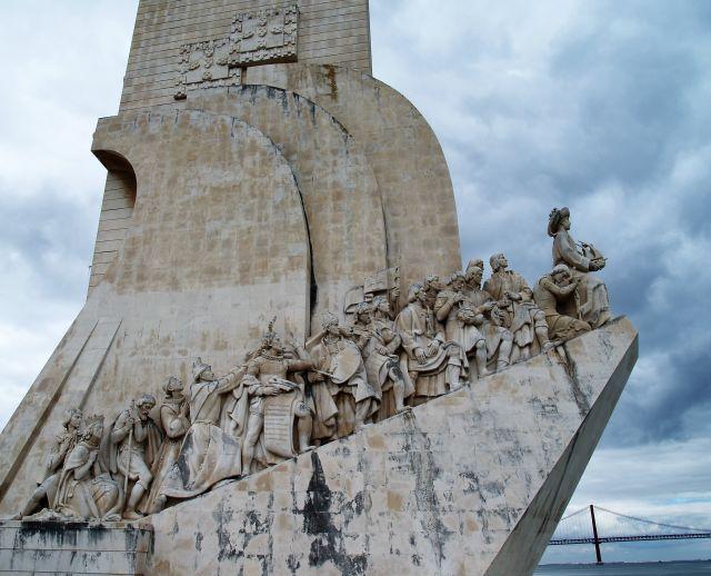 Das Denkmal besteht aus hellem Gestein. Schräg nach oben - wie auf einem Schiff - stehen verschiedene zeitgenössische Personen.