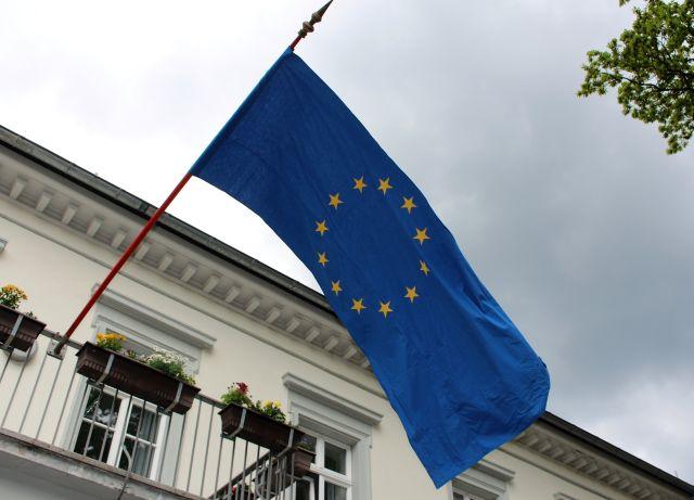Die blaue Fahne der EU mit den goldfarbenen Sternen flattert an einem hellen Gebäude.