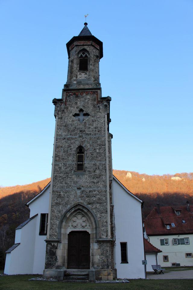 Der Turm der Kirche ist aus quadratischen Tuffsteinen aufgemauert. Die anderen Teile der Kirche sind weiß getüncht.