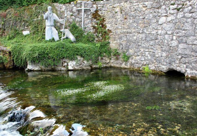 Im Vordergrund ein kleiner Teich mit grünen Pflanzen und weißen Blüten, das zufließende Wasser verlässt diesen mit einem kleinen Strudel. Im Hintergrud ein Kreuz an einer Natursteinmauer und daneben eine Skultur des Heiligen Gallus mit einem Bären.