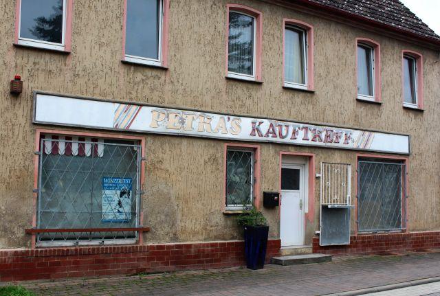 Bräunliche Hausfassade, ein leeres Ladengeschäft mit dem halb abgefallenen Titel 'Petra's Kauftreff'.