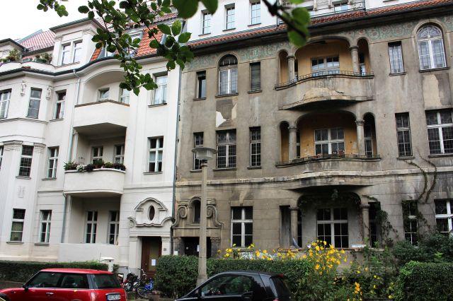 Der linke Gebäudeteil ist renoviert mit heller Fassade, der rechte im tristen braun-grau der DDR-Zeit, die Fassade bröckelt.