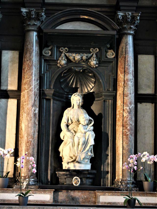 Madonna mit Kind aus weißem Marmor, links und rechts rötlich-braune Marmorsäulen und Blumen.
