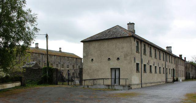Ein großes Gebäude mit gräulich-bräunlicher Farbe. Leicht versetzt dahinter ein zweites Haus mit zwei Stockwerken.