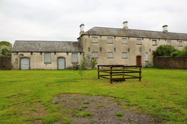 Ein mehrstöckiges Gebäude mit vergilbter Fassade, daneben einstockig das frühere Totenhaus. Im Innenhof wächst Gras, abgeschrankt der Brunnen.