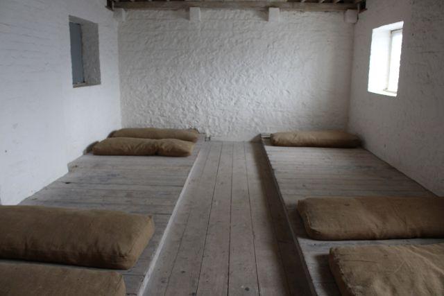 Auf einem Holzpodest liegen Säcke mit Stroh gefüllt. Die Wände sind weiß mit einer Kalkfarbe gestrichen.