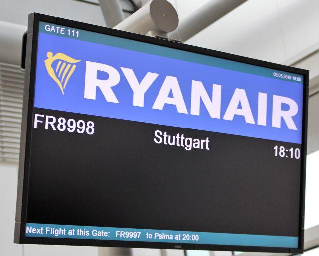Auf einer dunklen Anzeigetafel steht 'Ryanair' mit dem Flug nach Stuttgart um 18.10. Die Zeit zeigt bereits 18.08, doch weit und breit kein Flugzeug.