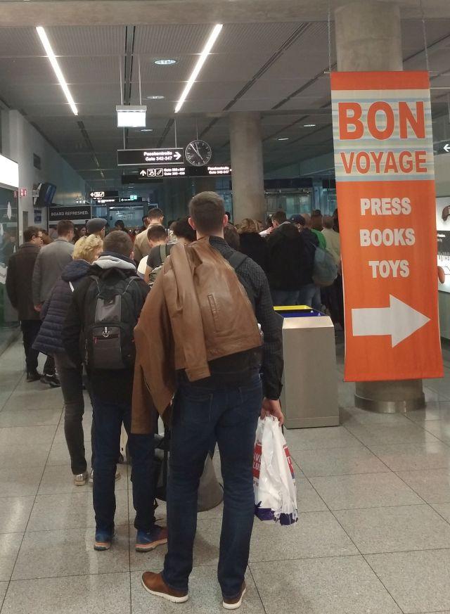 Menschen stehen an, daneben ein Schild mit orangener Farbe und dem Aufdruck 'Bon voyage'.