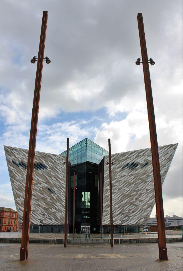 Im Vordergrund stählerne Pfosten, die die Stelle markieren, an der die Titanic gebaut wurde. Dahinter dassilbern glänzende Titanic-Museum in Belfast.