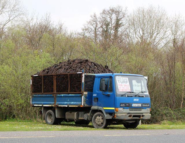 Blauer Lkw, voll beladen mit Torfbrocken. Ein Schild weist darauf hin, dass die ganze Ladung gekauft werden kann.