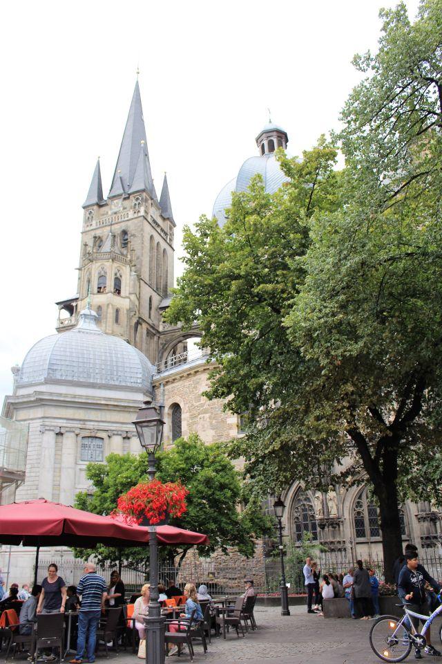 Derspitz zulaufende Turm des Doms im Hintergrund, weitere Gebäudeteile davor. Rechts ein grüner Baum, links im Vordergrund ein Straßencafe.