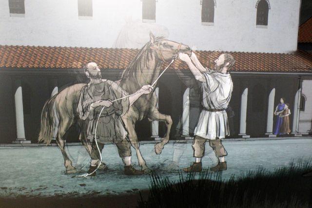 Visuelle Darstellung im Museum. Ein Mann hält ein Pferd am Zaumzeug, davor ein römischer Soldat.
