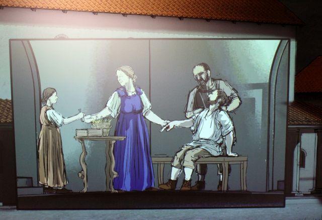Die Heilerin im blauen Kleid lässt sich ein Fläschchen mit Medizin reichen und hält den rechten - verletzten - Arm fest.