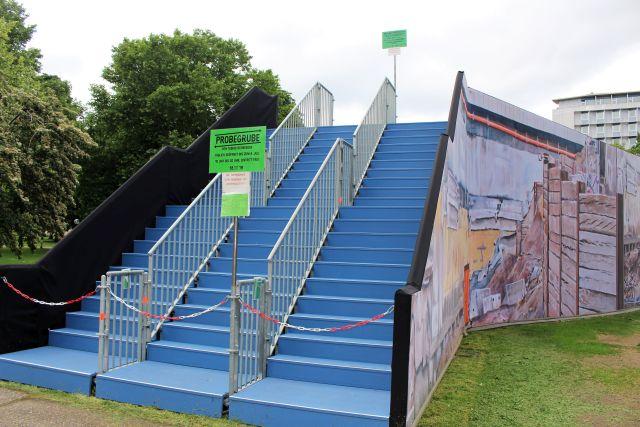 """Blaue Treppen führen zur """"Probegrube"""" hinauf. Vorne abgesperrt mit rot-weißen Ketten."""