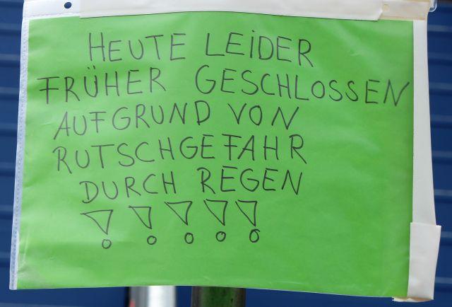"""Ein grünes Schild mit dem Text: """"HEUTE LEIDER FRÜHER GESSCHLOSSEN AUFGRUND VON RUTSCHGEFAHR DURCH REGEN !!!!!"""" -in: """"Stuttgart: Ein Wischmopp für die Kulturschickeria! Die """"Probegrube"""" vor dem Schauspielhaus wegen Regen geschlossen"""" – www.deutschland-geliebte-bananenrepublik.de"""