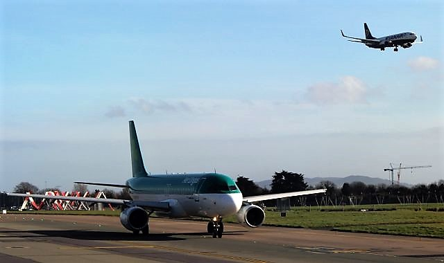 Ein Flugzeug von Ryanair im Landeanflug, der Aerlingus-Fliefger wartet am Boden.
