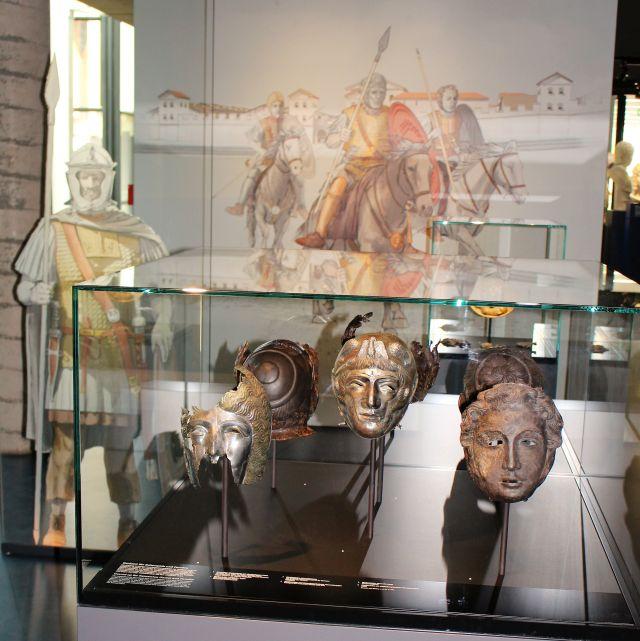 In einer Glasvitrine im Vordergrund Masken aus Metall, dahinter an der Wand eine Installation mit römischen Reitersoldaten.