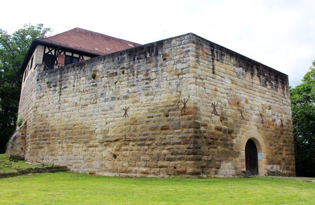 Eine zehn Meter hohe Mauer aus Buckelquadern sichert ddie Burg. Im oberen Teil ist noch ein kleiner Teil des roten Dachs des Hauptgebäudes zu sehen.