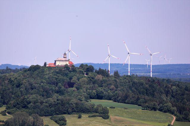 Das Schloss Baldern mit heller Fassade und rotem Ziegeldach umgeben von Windkraftanlagen.