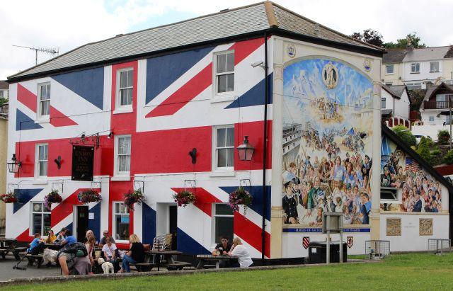 Ein Gebäude mit der britischen Flagge in blau, rot, weiß bemalt. Davor sitzen Gäste des Pubs.