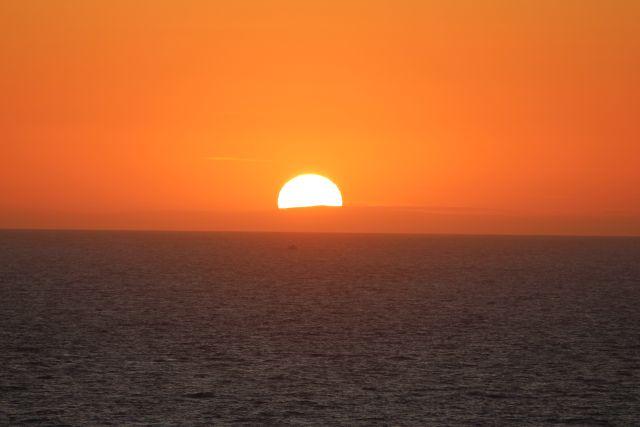 Rötlicher Sonnenuntergang über dem Meer an der Küste von Cornwall.