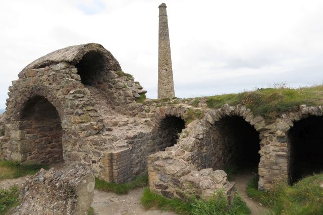 Ruinen mit Rundbögen sind von der Arsengewinnung zurück geblieben. Im Hintergrund ein Kamin.