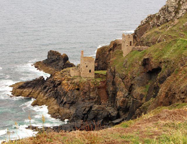 Zwei frühere Maschinenhäuser aus hellem Naturstein stehen unterhalb der Klippe nahe am Meer auf vorgelagerten Felsen.