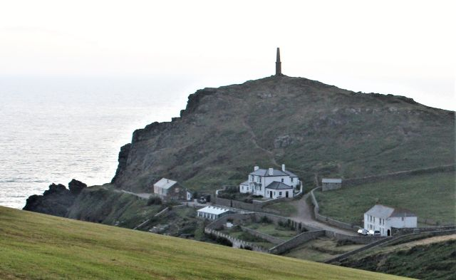 Auf dem Cape Cornwall erhebt sich ein Kamin. Unterhalb die früheren Gebäude der Mine und ein umfrideter Garten.
