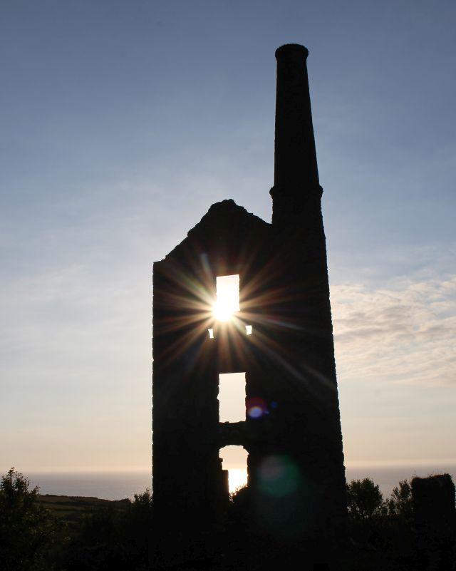 Die Sonne blitzt durch das oberste Fensterloch eines ehemaligen Maschinenhauses. Danben der Kamin in der Abendstimmung.