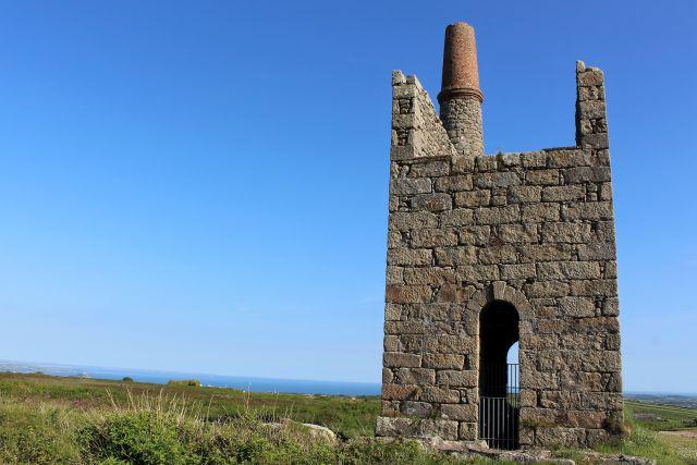Die einsame Ruine eines Maschinenhauses mit Kamin. Im Hintergrund das Meer.