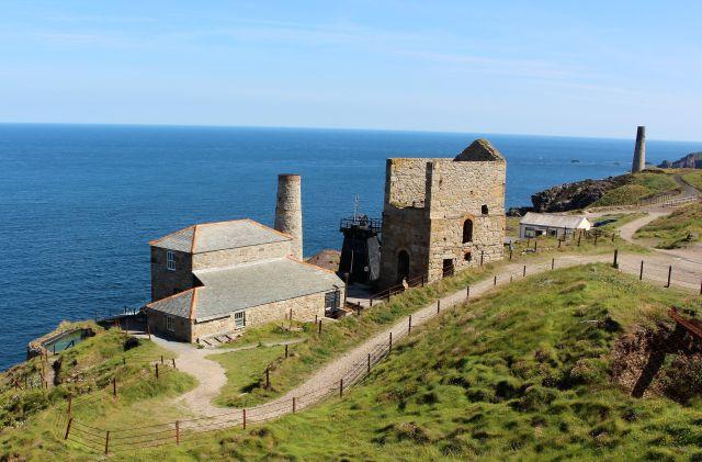 Die Gebäude der Levant Mine in Cornwall wurden mit Natursteinen errichtet. Zu sehen sind ehemalige Maschinenhäuser und ein Kamin. Im Vordergrund ein mit einem Gitter gesicherter ehemaliger Schacht.