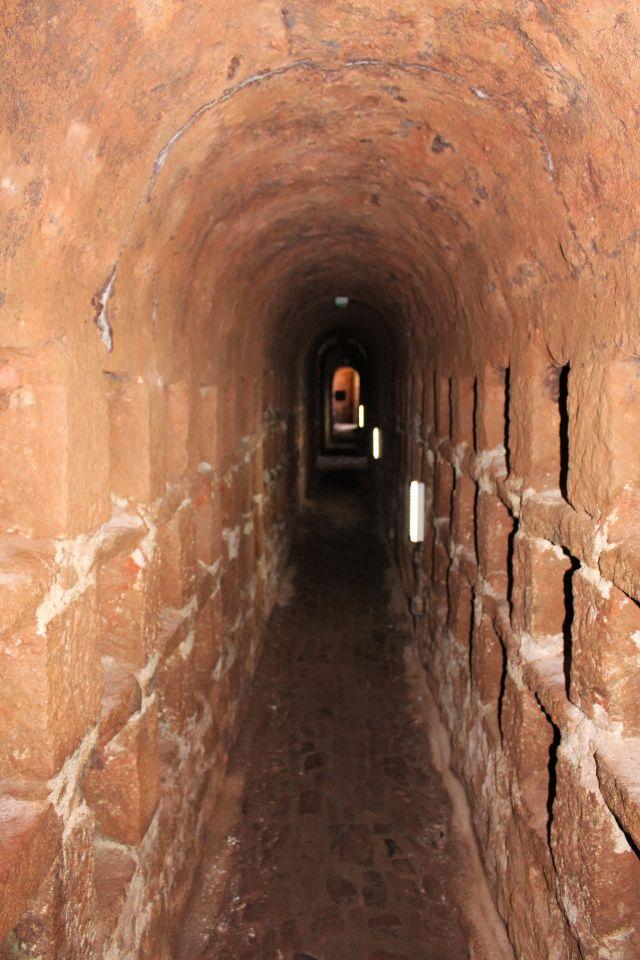 Unterirdischer gemauerter Zugang zu einer Schachtanlage. Rechteckige Aussparungen im rötlichen Gestein dienten der Unterbringung der Kopfbedeckungen.