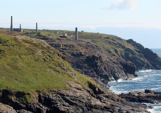 Vier Kamine ehemaliger Bergwerke und Ruinen von Maschinenhäusern an der Küste Cornwalls.