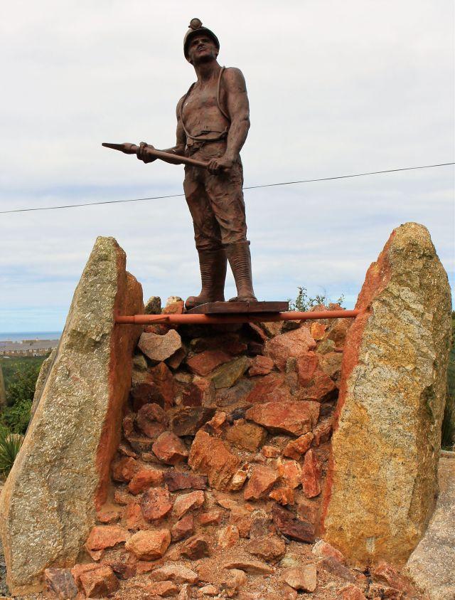 Skulptur eines Bergarbeiters mit Spitzhacke auf herausgebrochenem Gestein.