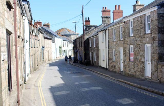 Die Hauptdurchgangsstraße in St. Just. Links und rechts eine Häuserzeile. Die meisten Gebäusde aus Naturstein.