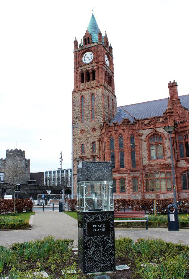 Der Turm der Guildhall im Hintergrund, im Vordergrund in einem Glaskasten die 'Peace Flame'.