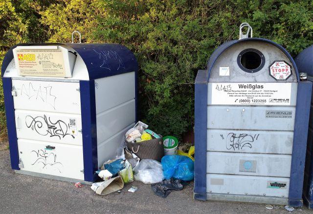 Links ein heller Container für Altkleider, rechrs ein grauer Container für Weißglas. Dazwischen abgelagerter Hausmüll in Säcken und Tüten.