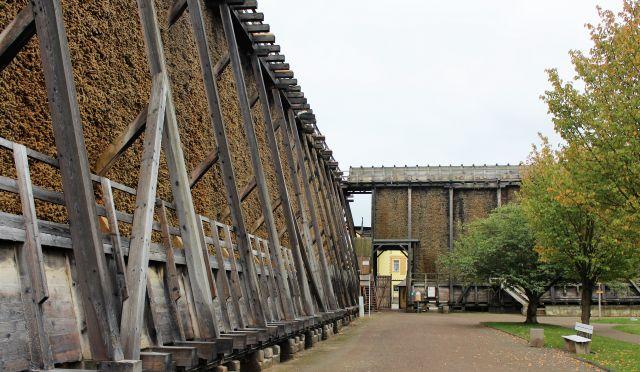 Konstruktion mit Holzstämmen ohne Rinde trägt die Gesamtkonstruktion. In ihr befinden sich die Reisigbündel. Das Gadoerwerk verläuft links im Bild und setzt sich dann im rechten Einkel in Bad Dürrenberg fort.