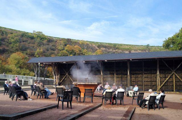 Menschen sitzen auf Stühlen rund um einen Solezerstäuber im Kurpark von Bad Kreuznach.