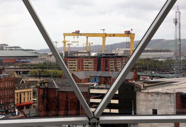 Die beisen gelben Kranaanlagen im Hintergrund. Im Vordergrund die Verstrebungen der Verglasung am Victoria Square, dazwischen Gebäude der Stadt Belfast.